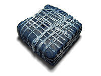 A piece of hardened indigo plant dye from India, about 2.5 inches (6 cm) square prepared for shipment