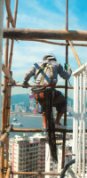 A bamboo scaffolder who wears safety harness is climbing on the scaffolds. 1990s