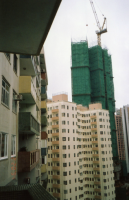 A high-rise building under construction is covered completely by bamboo scaffolds to form working platforms and scrambling units. 2007