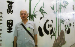 Dr. Dan Waters standing in front of the mural of pandas and bamboo at the Sheung Shui Training Centre. 2007