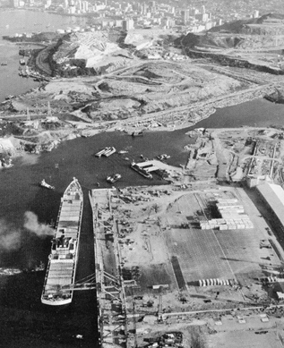 September 1972-first purpose built container ship to berth at the new terminal at Kwai Chung. Berth and container handing areas still incomplete. Gin Drinkers Bay continues to be reclaimed. Tsuen Wan town is in the background.