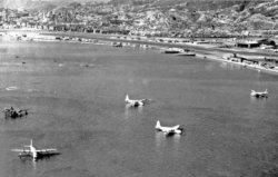 11 RAF Sunderlands And A US Navy Martin Mariner Flying Boats At Rest In The Bay Off Kai Taks Seawall